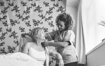 caregiver assisting elder woman get dressed
