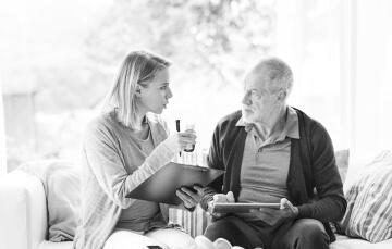 caregiver and elder man talking