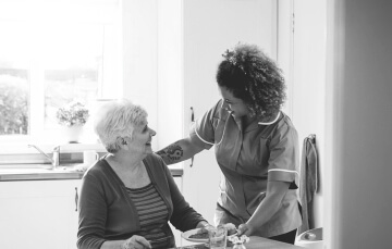caregiver preparing meal for elder woman