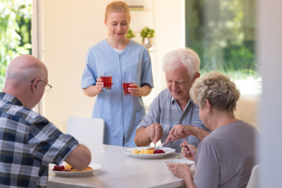 caregiver serving meal to the seniors