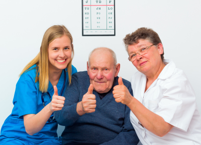 elder man and his caregivers showing thumbs up