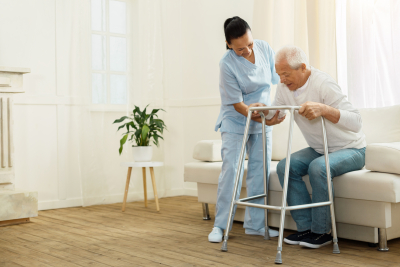positive cheerful caregiver smiling and helping her patient to stand up