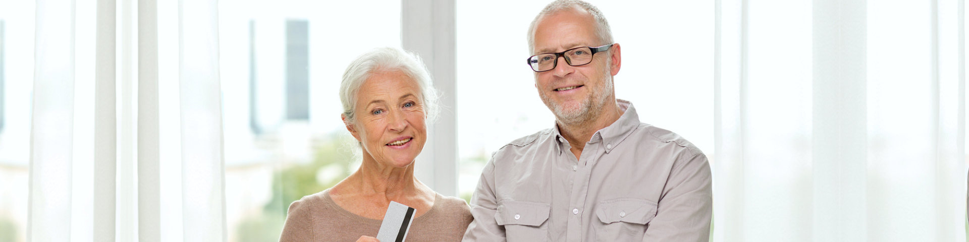 Happy senior couple with tablet pc and credit card