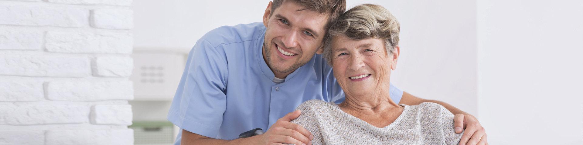 Male nurse hugging his senior woman patient