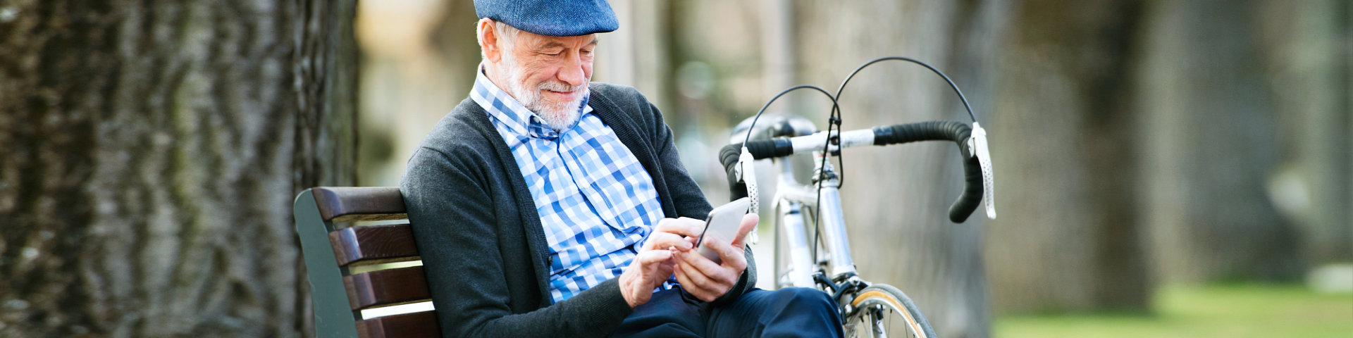 Senior man with bicycle in town, holding smart phone
